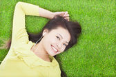 Pretty woman listening music and lying on a meadow — Stock Photo