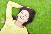 Smiling  woman listening music and lying on a meadow — Stock Photo