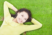 Beautiful  woman holding head and lying on a meadow — Stock Photo