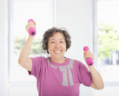 Happy senior woman working out with dumbbells at home — Stock fotografie