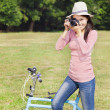 Stock Photo: Female photographer holding camerand sitting bike