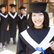 Stock Photo: Pretty  female college graduate holding diplomwith classmates