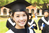Beautiful female college graduate with classmates at ceremony — Stock Photo