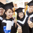 Stock Photo: Group of graduating students holding diplomand thumb-up
