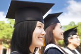 Smiling female college graduate standing with classmate — Stock Photo