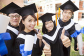 Group of graduating students holding diploma and thumb-up  — Stock Photo
