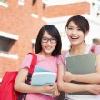 Stock Photo: Two smiling students holding books  at campus