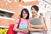 Two smiling students holding books  at campus — Stockfoto