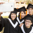 Stock Photo: Group of graduates  taking picture with cell phone
