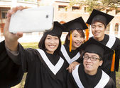 Group of graduates  taking picture with cell phone — Stockfoto