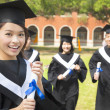 Stock Photo: Female college graduate with classmates and holding diploma