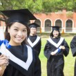 Stock Photo: Smiling college graduate show diploma