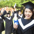Stock Photo: Happy college graduate holding diplomwith friends