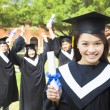 Stock Photo: Beautiful female college graduate holding a diploma at ceremony