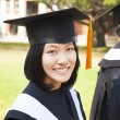 Beautiful female college graduate with classmates at ceremony — Stock Photo #41889861
