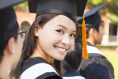 Smiling woman standing out from a graduation group — Stock Photo
