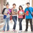 Group student holding books and standing at school — Stock Photo