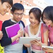 Stock Photo: Group of students discussing homework by using tablet