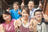 Group of happy students with thumbs up — Stockfoto