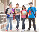 Group student holding books and standing at school — Foto de Stock