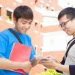 Stock Photo: Two students using cell phone  to discuss