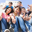 Happy and smiling students thumbs up together — Stock Photo