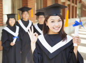 Young college graduate holding diploma  and make a gesture — Stock Photo