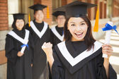 Happy college graduate holding diploma  and make a fist — Stock Photo