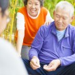 Seniors play weiqi with friends in the park — Stok fotoğraf