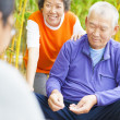 Seniors play weiqi with friends in the park — ストック写真