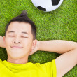 Young man lying on a meadow with a football — Stock Photo #42718257