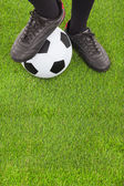 Soccer player's feet  and football on field  — Stock Photo