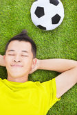 Young man lying on a meadow with a football — Photo