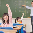 Asian pupils raising hands during the lesson — Stock Photo