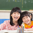 Happy little girls in the classroom — Stock Photo
