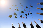 Happy young graduates throwing hats — Stock Photo