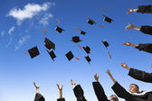 Students throwing graduation hats in the air celebrating — Stock Photo