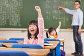 Happy pupils raising hands during the lesson  — Stock Photo