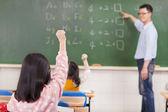 Elementary school students raising hands — Stock Photo