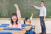 Asian pupils raising hands during the lesson  — Foto Stock