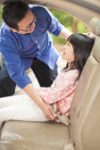 Father help daughter to fasten a seat belt — Stock Photo