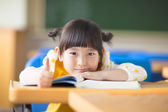 Smiling kid lie prone on a desk and thumb up — Stock Photo