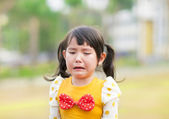 Crying little girl in the park — Stock Photo