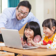 Teacher teaching children with a laptop — Stock Photo