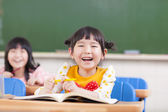 Happy children studying in a classroom — Stockfoto