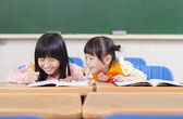 Cute little student  look her classmate homework — Foto Stock
