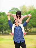 Happy daughter sitting father's shoulder  — Zdjęcie stockowe