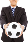 Smiling businessman show a soccer — Stock Photo