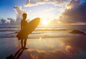 Surfer man standing on beach and holding a surfboard — Stock Photo