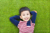 Glada barn ljuger och håller hans huvud på en äng — Stockfoto